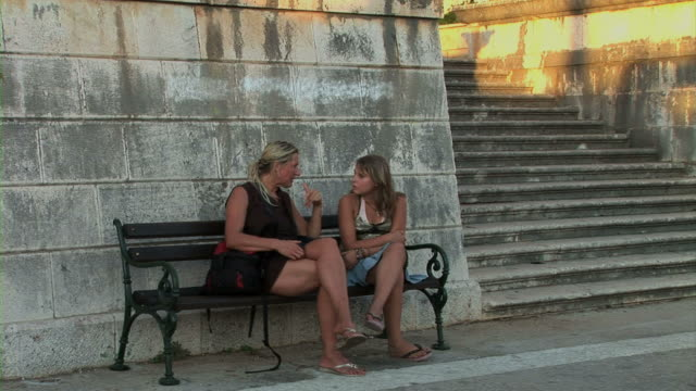mother and daughter resting on bench - cross legged stock videos & royalty-free footage