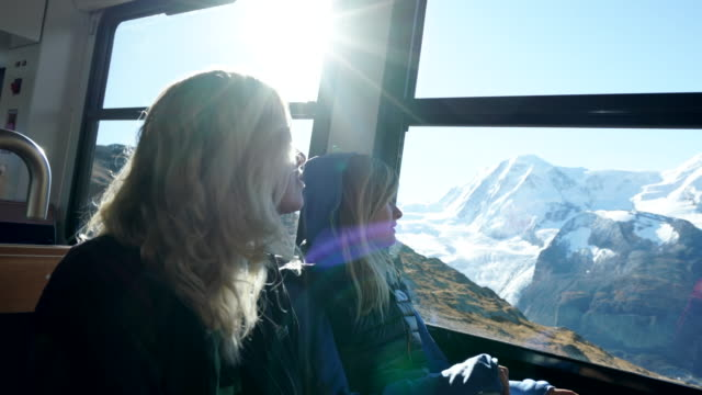mother and daughter ride alpine train along glacier - adult offspring stock videos & royalty-free footage