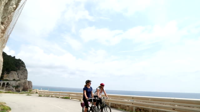 mother and daughter ride bikes along coastal road - sports helmet stock videos and b-roll footage