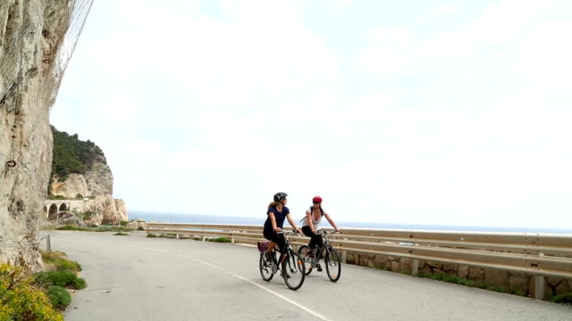 mother and daughter ride bikes along coastal road - helmet stock videos & royalty-free footage