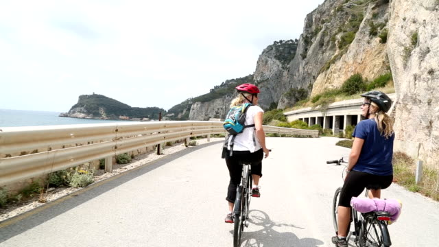mother and daughter ride bikes along coastal road - pedal pushers stock videos & royalty-free footage
