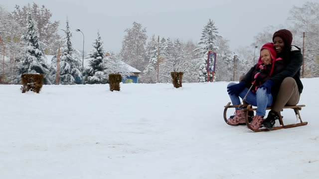 mother and daughter rides the sledge in the winter park - sliding stock videos & royalty-free footage