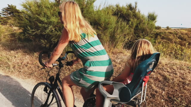 mother and daughter riding bicycle on sunny day - cycling stock videos & royalty-free footage