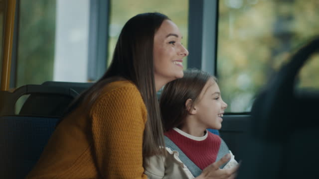 mother and daughter riding on the bus together - cable car stock videos & royalty-free footage
