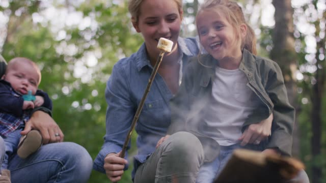 mother and daughter roasting a marshmallow - camp fire stock videos & royalty-free footage