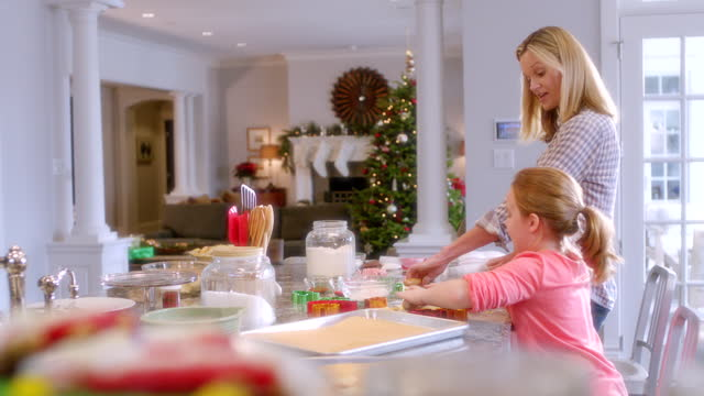 Mother and daughter roll out and flatten cookie dough in kitchen (dolly-shot)