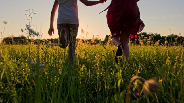 vidéos et rushes de ts mère et fille courir dans l'herbe - robe d'été
