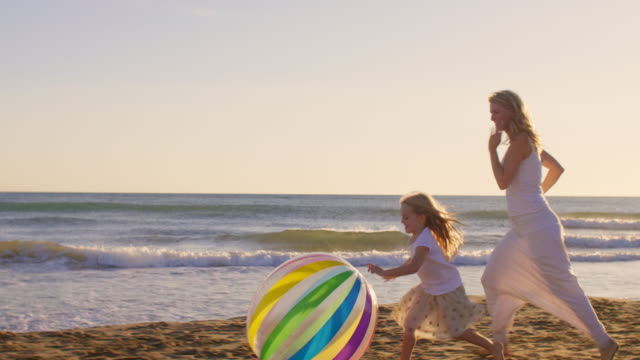 Mother and daughter running on beach with beach ball