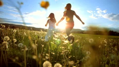vídeos y material grabado en eventos de stock de super una persona madre e hija corriendo hacia el sol - niñas