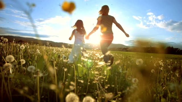 stockvideo's en b-roll-footage met super slo mo mother and daughter running to the sun - field