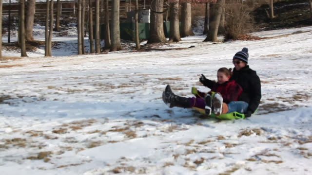 mother and daughter scream down a partially snowy hill on a toboggan passing young boy on snowboard - kelly mason videos stock videos & royalty-free footage