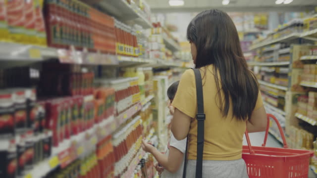 mother and daughter shopping at supermarket - sauce stock videos & royalty-free footage