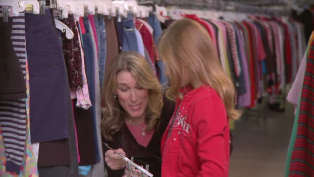 cu mother and daughter (8-9) shopping for clothes together in thrift store / morris, illinois, usa - second hand stock videos & royalty-free footage