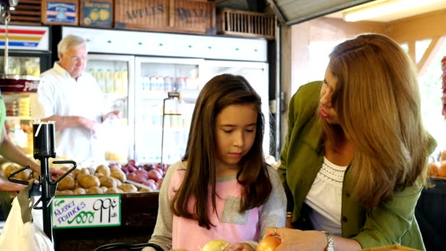 Mother and daughter shopping in outdoor farmer's market