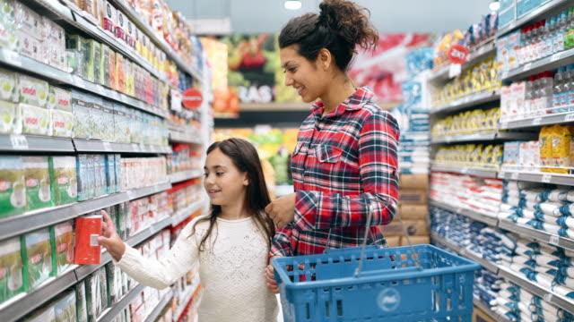 vidéos et rushes de achats de mère et de descendant dans le supermarché - panier courses