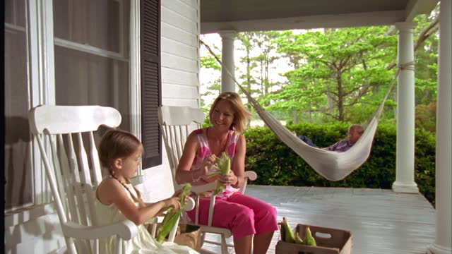 A mother and daughter shuck corn while Dad relaxes in the porch hammock.