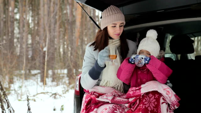 mother and daughter sit in the open trunk of the car and drink tea. - picnic stock videos & royalty-free footage