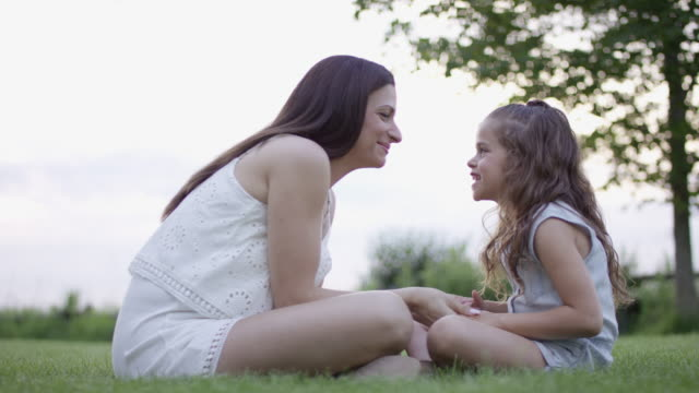 vídeos de stock e filmes b-roll de mother and daughter sitting cross-legged in a field - cross legged