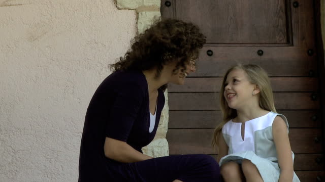 MS Mother and daughter sitting on a doorstep / France