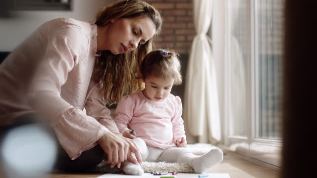 Mother and daughter sitting on floor and drawing together