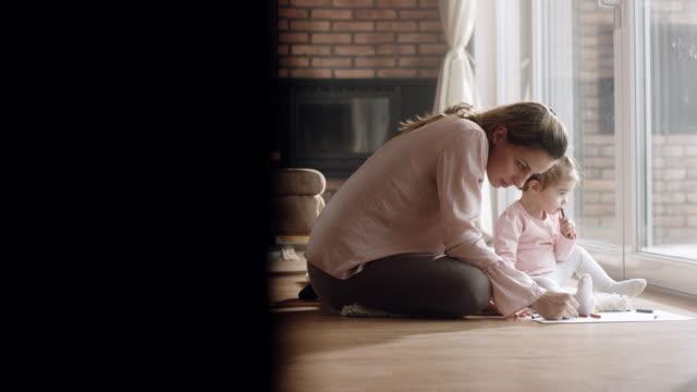 vídeos y material grabado en eventos de stock de madre e hija sentada en el piso y cohesionar - daughter