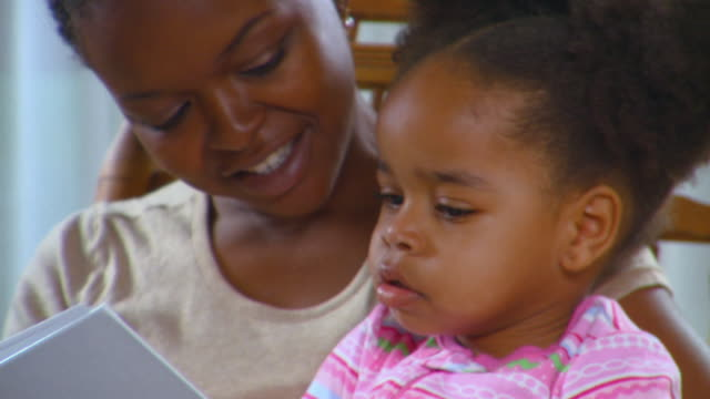 cu, mother and daughter (2-3) sitting on rocking chair and reading book, richmond, virginia, usa - picture book stock videos and b-roll footage