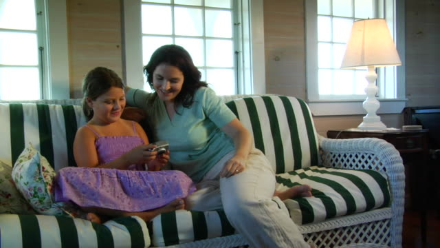 ms, mother and daughter (8-9) sitting on wicker couch, looking at digital camera, north truro, massachusetts, usa - digital camera stock videos & royalty-free footage