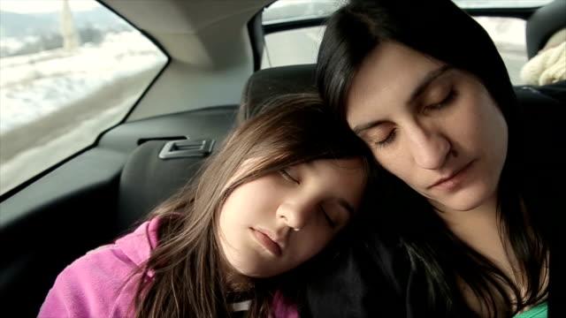 Mutter und Tochter schlafen im hinteren Sitz im Auto