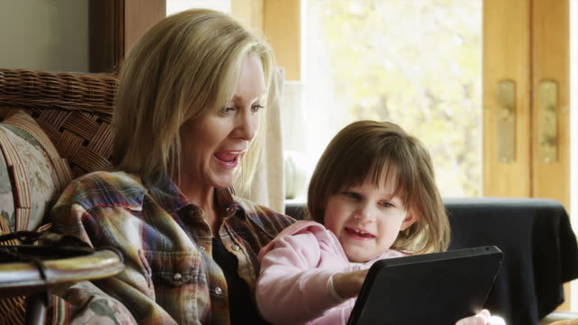 zi cu mother and daughter (4-5) slitting in wicker armchair and looking at digital tablet / cedar hills, utah, usa - touching stock videos and b-roll footage