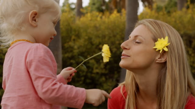 Mother and daughter smelling yellow flower in park