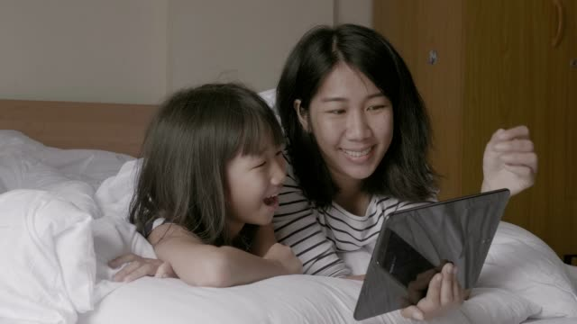 mother and daughter spending time together and playing  tablet  on bed - daughter stock videos & royalty-free footage