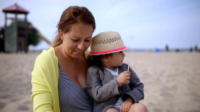 mother and daughter spending time together on a beach - lollipop stock videos and b-roll footage