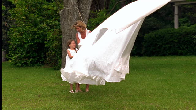 A mother and daughter stand at the end of a clothesline.