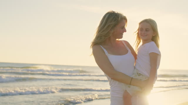 Mother and daughter standing on beach hugging and playing in sunset