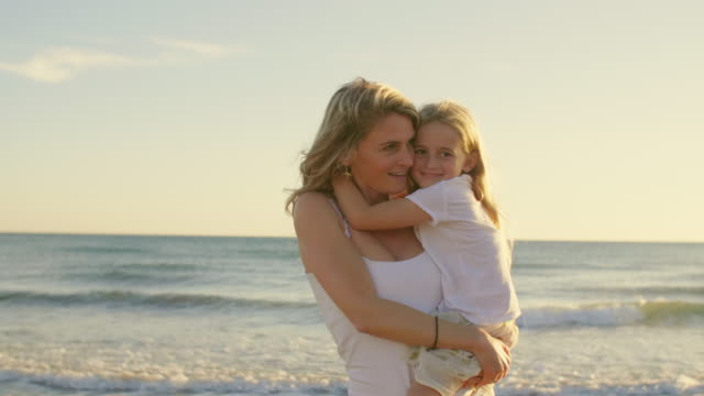 Mother and daughter standing on beach hugging and playing