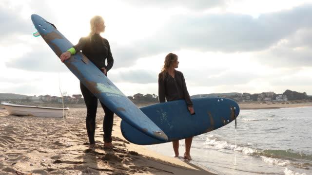 vidéos et rushes de la mère et le descendant surfent ensemble, à la plage - commencement