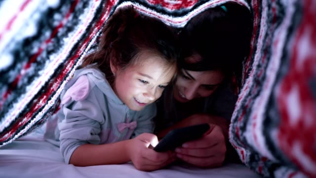 mother and daughter surfing the net in bed - tapping stock videos & royalty-free footage