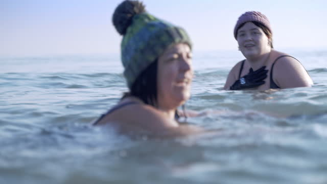 mother and daughter swimming together in a very cold sea in winter - cold temperature stock videos & royalty-free footage