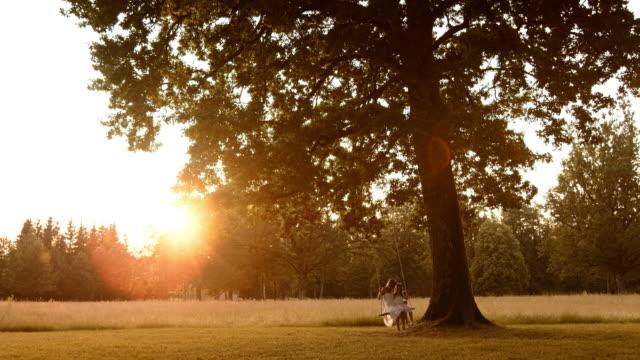SLO, MO, TD Mutter und Tochter schwingen bei Sonnenuntergang