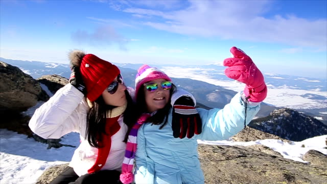 mother and daughter take selfie on the top of the mountain at winter - ski stock videos & royalty-free footage