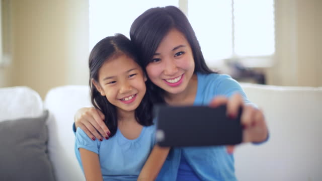 ms mother and daughter taking a photo together. - 思い出点の映像素材/bロール