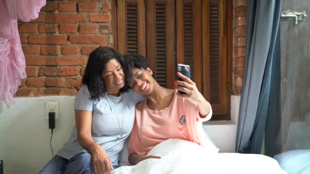 mother and daughter taking a selfie at bed - mother's day stock videos & royalty-free footage