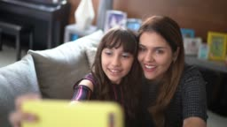 Mother and daughter taking a selfie at home