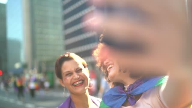 vídeos de stock, filmes e b-roll de matriz e filha que tomam um selfie durante a parada de lgbtqi - evento