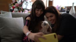 Mother and daughter taking a selfie with dog at christmas time