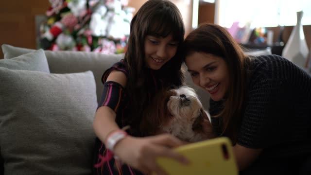 クリスマスの時期に犬と一緒に自分撮りをする母と娘 - photographing点の映像素材/bロール