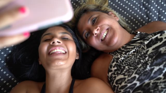 vídeos de stock e filmes b-roll de mother and daughter taking selfies with smartphone at bed - 18 19 anos