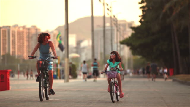 vídeos de stock, filmes e b-roll de mother and daughter talk while riding bikes down brazilian street - ciclismo