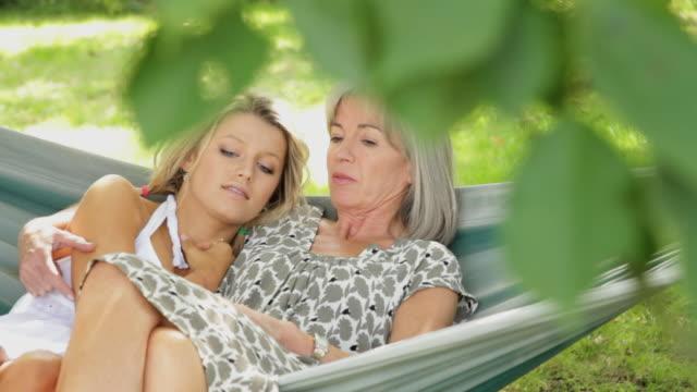 Mother and daughter talking in hammock in garden