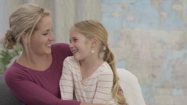 vidéos et rushes de mère et fille parler sur le canapé - prendre sur les genoux